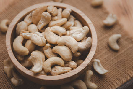 raw cashew nuts in wooden bowl on rustic table, healthy vegetarian snack
