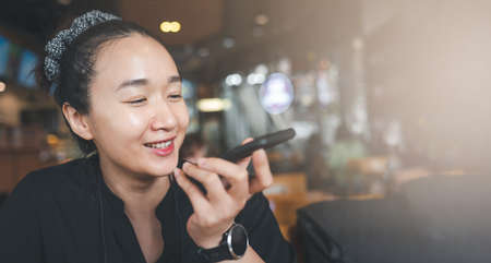 Young beautiful woman hold modern cellphone record voice message texting online, smart Asian female use smartphone activate virtual digital assistant on gadget, female have call on speakerphone on cell.