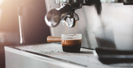 fresh morning espresso coffee with beautiful tiger crema pouring through the bottomless portafilter Espresso shot from coffee machine