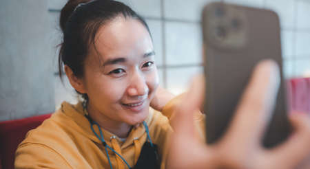 Young Asian teenager woman take Selfie at cafe, female using smartphone making vlog video to social media in coffee shop. Lifestyle woman relax in morning at cafe concept. freelance lift style. Reklamní fotografie