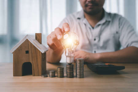 male hand holding a light bulb with coins stacking and house model on desk. The concept of installment and reduction of home loan interest, saving energy and money concept. 免版税图像
