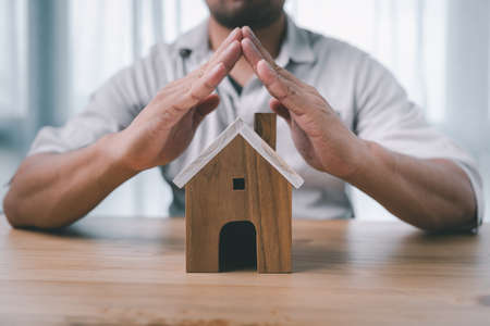 Property insurance and security concept. Protecting gesture of man and house model. Investment in real estate.