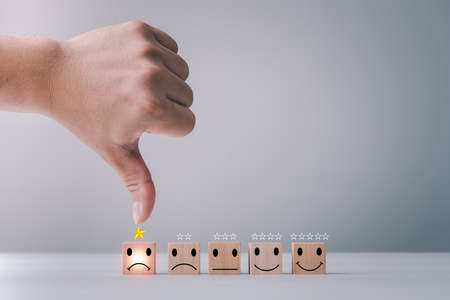 Customer service satisfaction survey concept. Business people or customers are thumbs down to show their satisfaction in service. human hand give a 1 star and unhappy face icon satisfaction rating.
