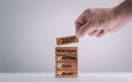 2021 New year resolution, Goal, Plan and action, human hand putting wood block with word.