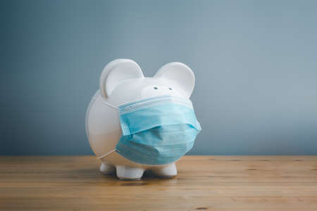 Piggy bank wearing surgical face mask. Global economy during coronavirus pandemic. Financial crisis, banking concept. saving and investment. Standard-Bild