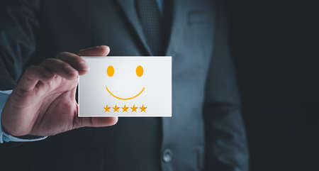 Customer Experience Concept, Businessman holding Card with Smiley Happy Face for his Satisfaction. feedback rating and positive customer review experience