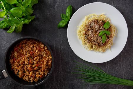 Traditional italian spaghetti Bolognese with meat and tomato sauce in a plate. Parmesan cheese, fresh tomatoes, basil, spices and herbs. Dark background. Top view.