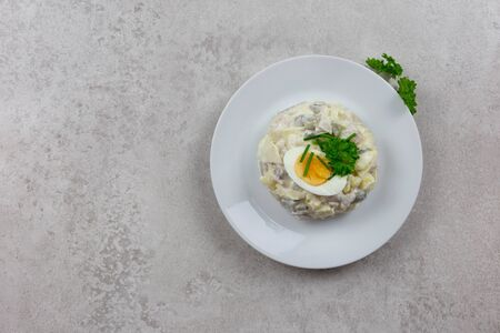 Salad with herring, eggs, apples and potatoes. Snack on a festive table on a light grey background. White plate, fresh herbs. Top view.
