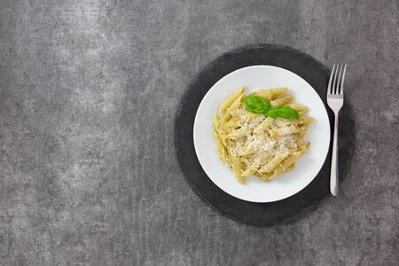 Traditional italian penne pasta with pesto, basil, tomatoes and parmesan. On a white plate, on a dark slate stand. Top view. Copy space.