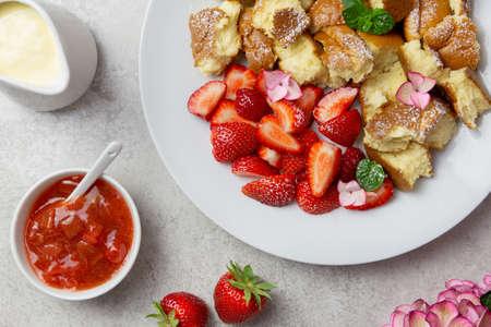 Kaiserschmarren or Kaiserschmarrn, traditional Austrian or German sweet pancake dessert, with berry, strawberry jam or rote grutze and vanilla pudding sauce. Top view.