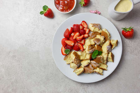Kaiserschmarren or Kaiserschmarrn, traditional Austrian or German sweet pancake dessert, with berry, strawberry jam or rote grutze and vanilla pudding sauce. Top view. Copy space.