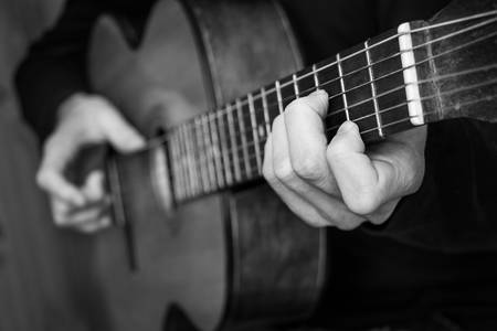 Man playing classical guitar. Black and white photo.