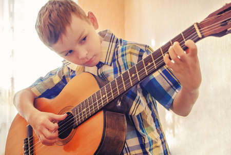 어쿠스틱 기타를 연주하는 것을 학습하는 소년. 파란색 셔츠에.