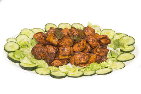 Spicy chicken tikka served in a tray with lettuce photo