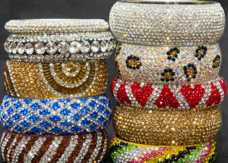 Crystal diamond stone metal bangles arranged in a pile photo