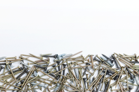 pile of metal screws on a white background