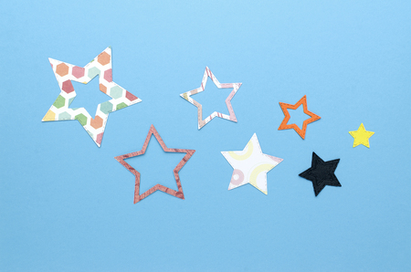 seven colorful flat paper stars on blue background