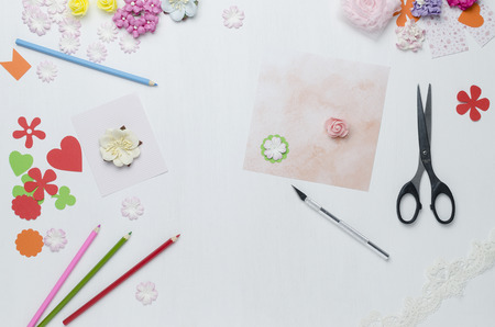 Paper flowers, colored pencils, scissors scattered on the table. The view from the top