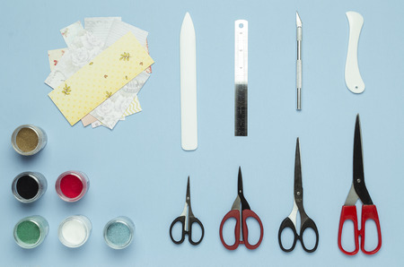 Neatly laid out tools for scrapbooking. Top view, blue background