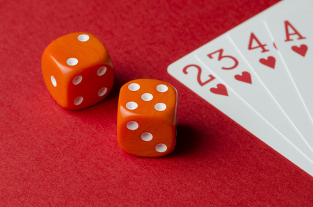 Two dice and playing cards on a red background. Close-up Stock Photo