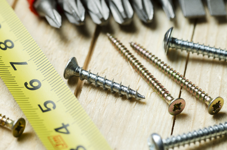 screws and measuring tape on wooden boards, closeup