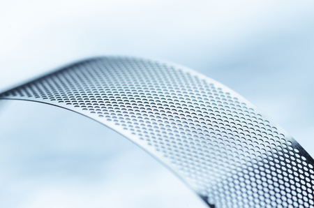 Shiny metal perforated tape abstract