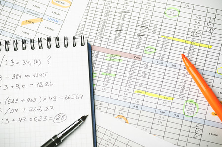 Financial tables on paper and notebooks with calculations, pen and highlighter Banque d'images - 102597570
