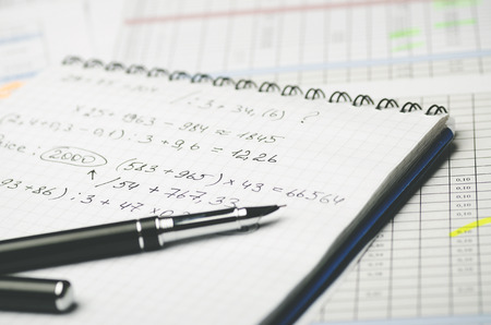 Paper notebook with accounting calculations and pen on the background of the table Banque d'images - 102575929