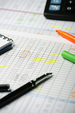 Financial calculations in a table on paper, pen, highlighter and calculator. Vertically Banque d'images - 102575932