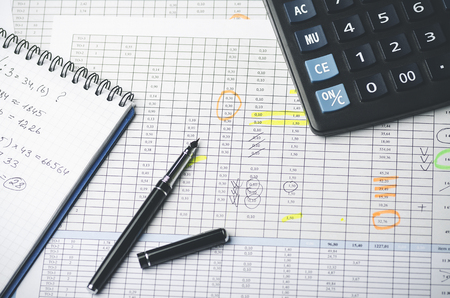 Tables with accounting figures, pen, paper notebook and calculator, top view