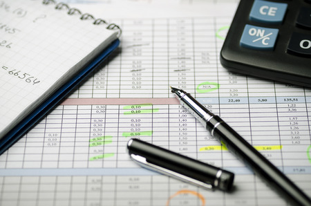 Accounting records in tables, a paper notebook with calculations and a black pen Banque d'images - 102592286