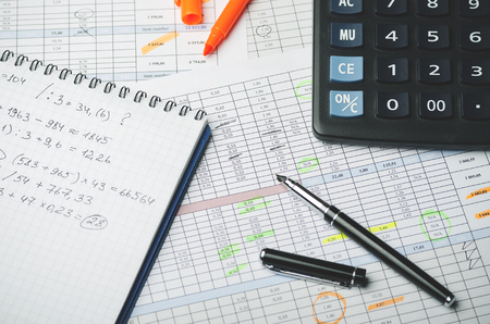 Accounting records in tables, a paper with profit calculations, a pen and a calculator Banque d'images - 102575931