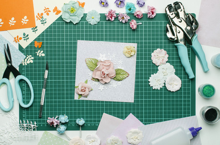 Multi-colored paper crafts on the cutting mat and scrapbooking tools, top view Banque d'images - 104598747