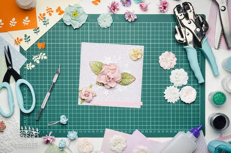 Multi-colored paper crafts on the cutting mat and scrapbooking tools, top view Banque d'images - 104598748