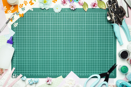 The cutting mat is surrounded by paper flowers, paper, tools and scrapbooking materials. Scrapbooking, top view, empty space in the center Banque d'images - 104598752