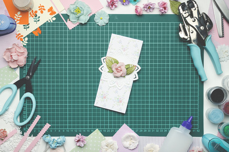 Multi-colored paper card on the cutting mat, tools and materials for scrapbooking, top view Banque d'images - 104598755
