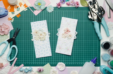 Multi-colored paper cards on the cutting mat, tools and materials for scrapbooking, top view Banque d'images - 104598756