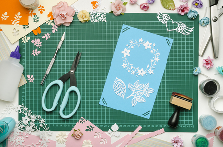 Multi-colored paper crafts on the cutting mat, tools and materials for scrapbooking, top view Banque d'images - 104598757