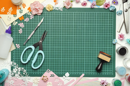 The cutting mat is surrounded by paper flowers, paper, tools and scrapbooking materials. Scrapbooking, top view Banque d'images - 104192288