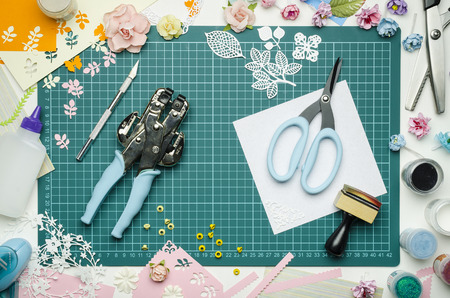 Multi-colored paper crafts on the cutting mat and scrapbooking tools, top view Banque d'images - 104192289