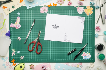 Homemade greeting card and tools on the cutting mat. Scrapbooking, top view Banque d'images - 104192295