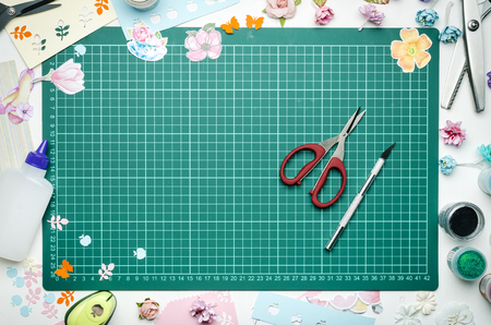 The cutting mat is surrounded by paper flowers, paper, tools and scrapbooking materials. Scrapbooking, top view Banque d'images - 104192292