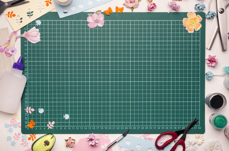 The cutting mat is surrounded by paper flowers, paper, tools and scrapbooking materials. Scrapbooking, top view Banque d'images - 104192293