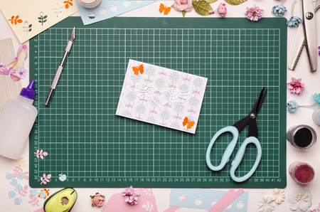 Homemade greeting card and tools on the cutting mat. Scrapbooking, top view Banque d'images - 104192294