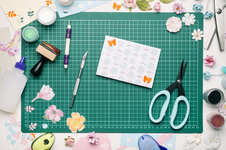 homemade postcard on green cutting mat, tools and scrapbooking materials, no hands Banque d'images - 104731107