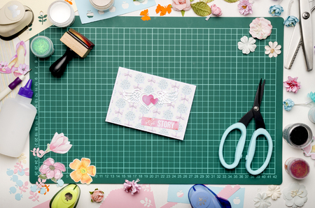 greeting card on green cutting mat, scrapbooking tools and materials, top view, no hands Banque d'images - 104731110