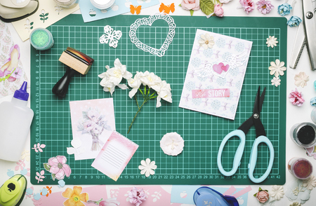 Paper flowers, a homemade card and tools for scrapbooking on the green mat for cutting. The view from the top, no hands Banque d'images - 104731112