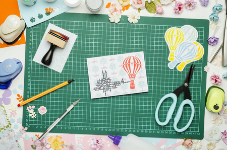 Multi-colored paper, homemade postcard and scrapbooking tools and materials on green mat for cutting, top view, no hands Banque d'images - 104730070