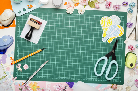 Multi-colored paper, scrapbooking tools and materials on green mat for cutting, top view, no hands Banque d'images - 104730072