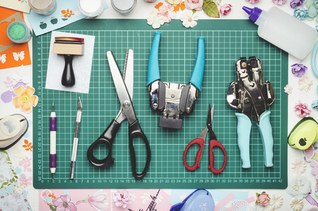 Tools for scrapbooking and creativity on green cutting mat. Top view Banque d'images - 104966575